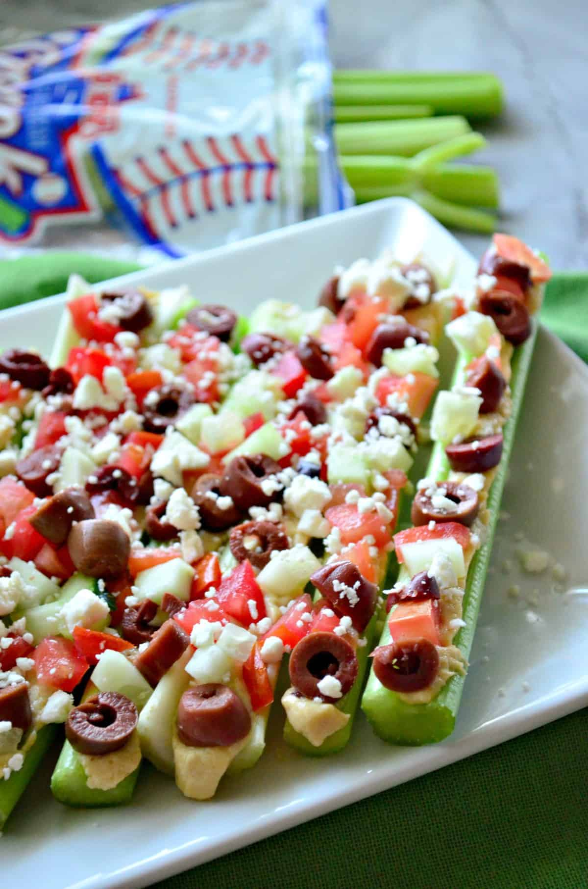 Plated celery sticks stuffed with hummus, feta, kalamata, and tomato with celery blurred in background.