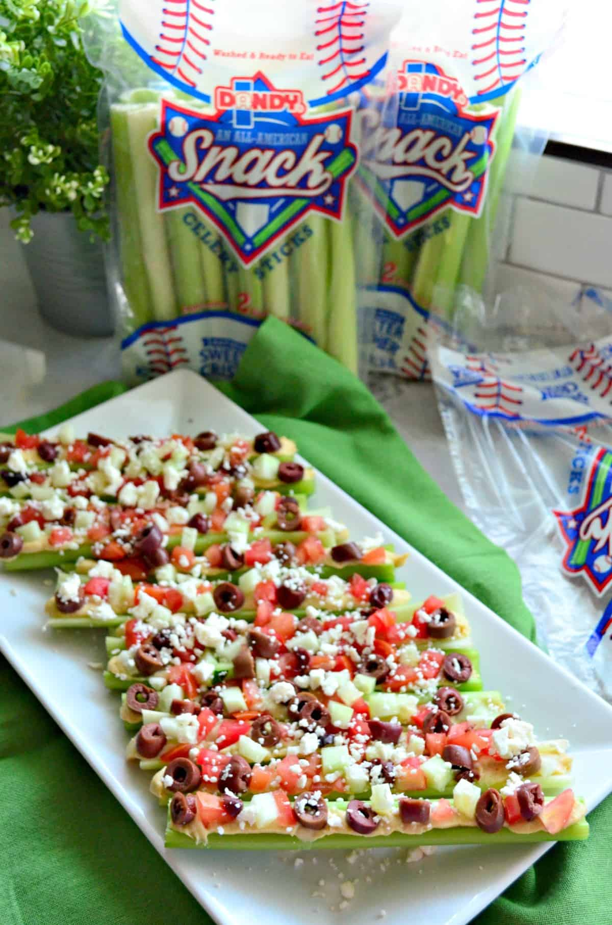 Plated celery sticks stuffed with hummus, feta, kalamata, and tomato in front of fresh celery.