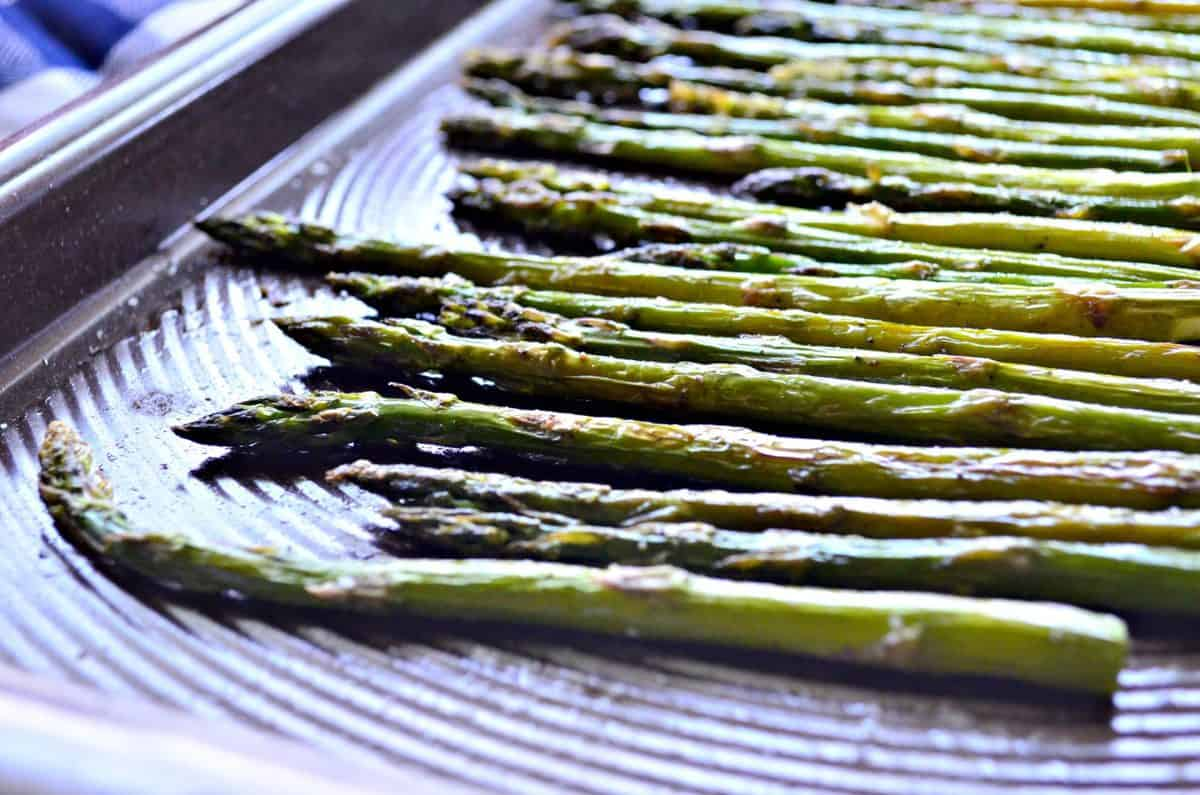 side view of roasted asparagus on sheet pan sprinkled with salt.