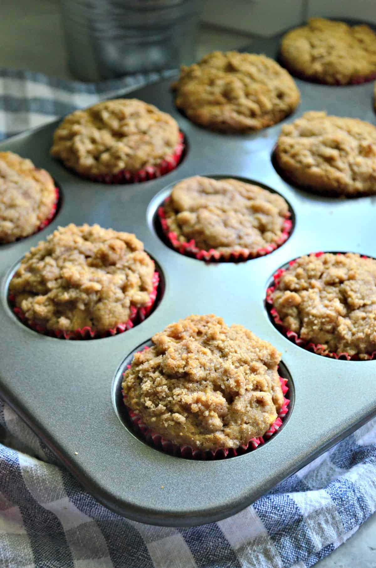 Apple Cinnamon Streusel Muffins in tin muffin pan with one in focus and the rest blurred.