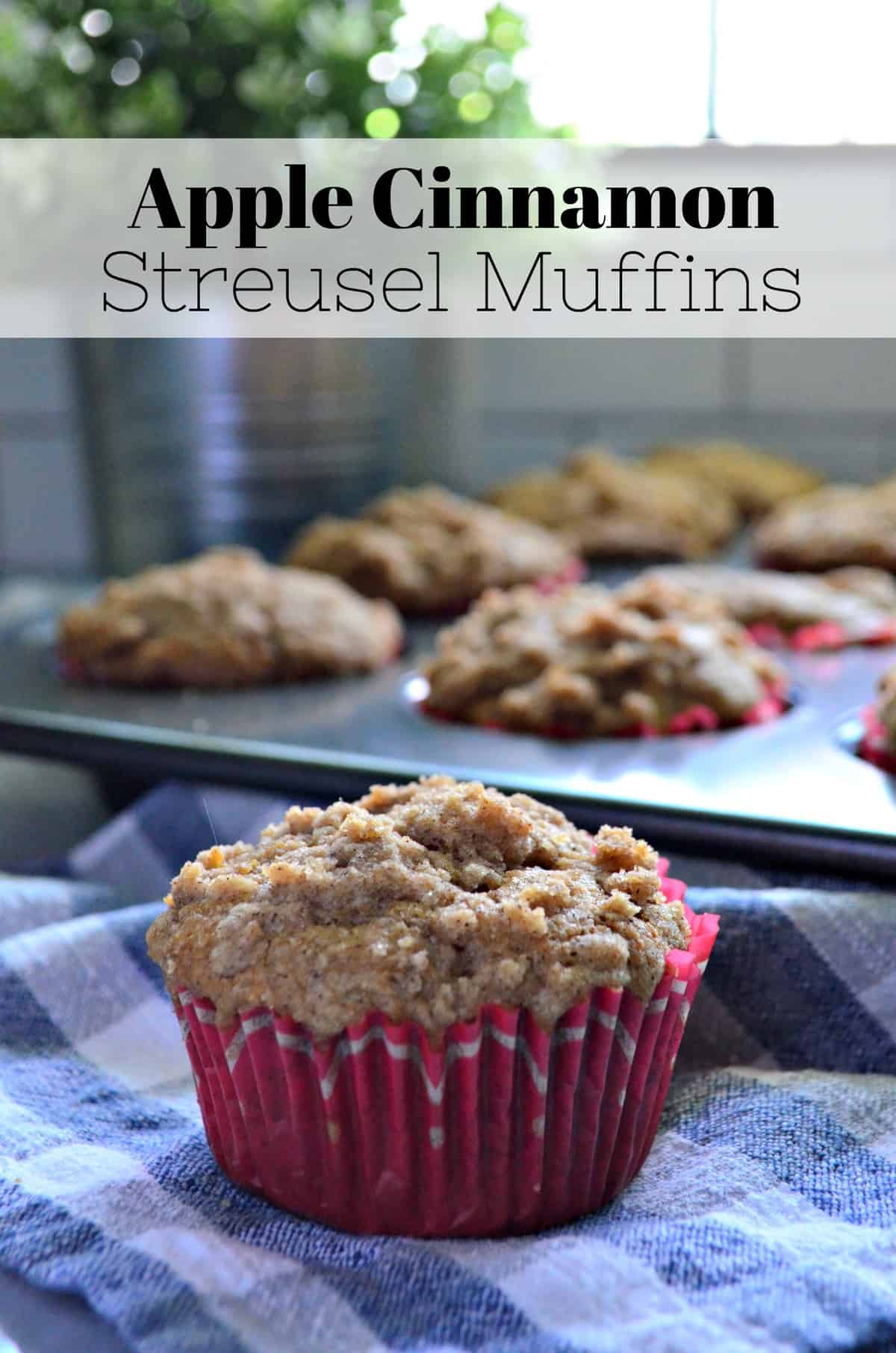 closeup apple streusel muffin in red muffin cup with muffin tin in background with title text.