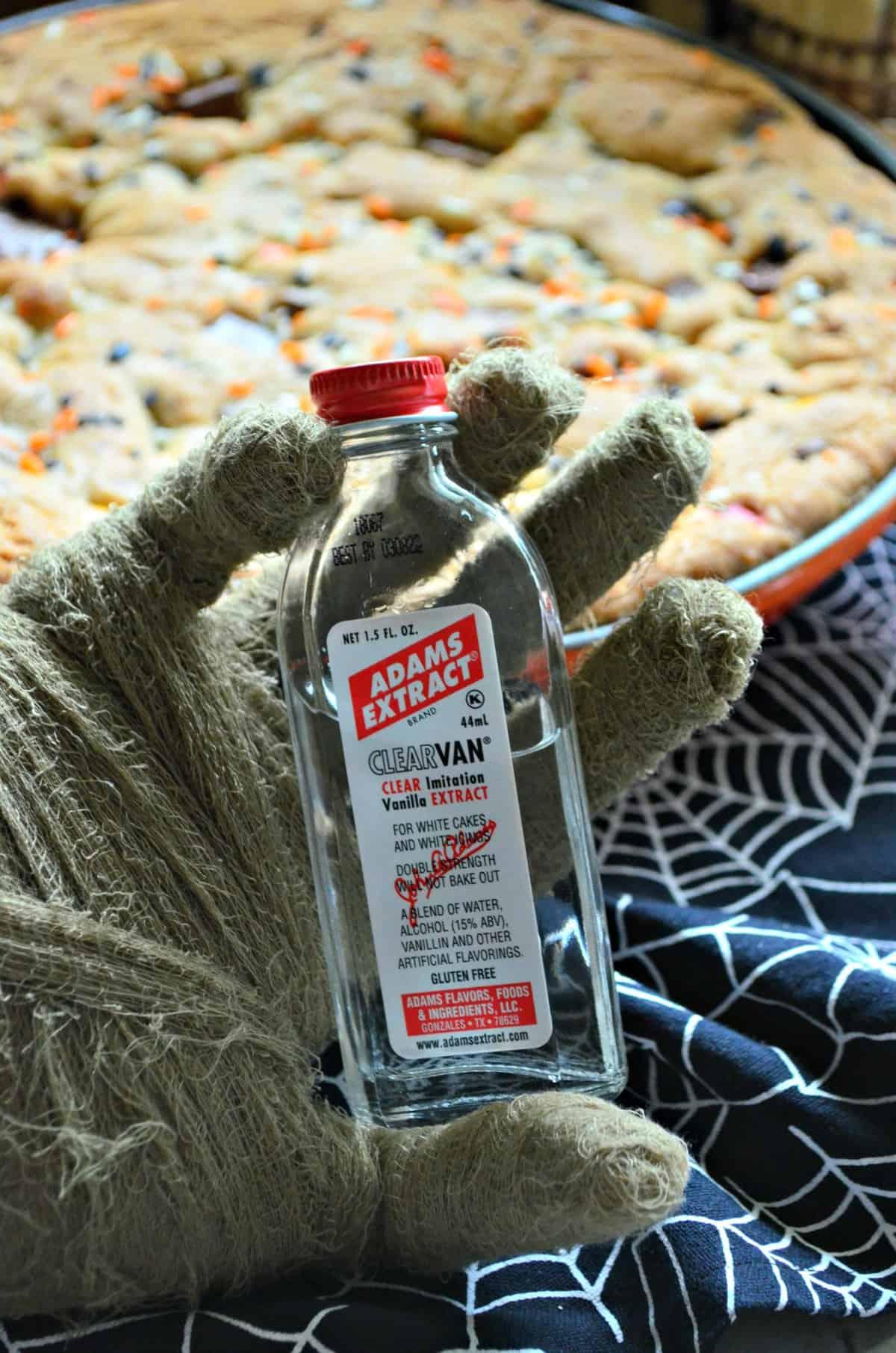 mummy hand holding up Adams Extract ClearVan imitation vanilla extract.