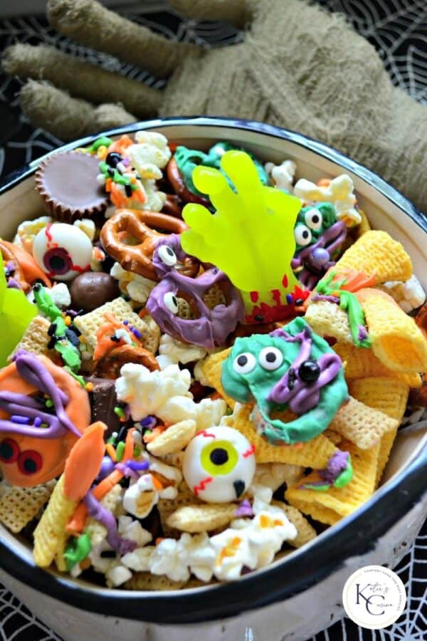 Close up of a bowl filled with popcorn, bugels, pretzels, and sweet treats.