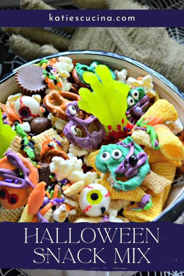 Close up of a bowl full of Halloween Snack Mix with recipe title text on image for Pinterest.