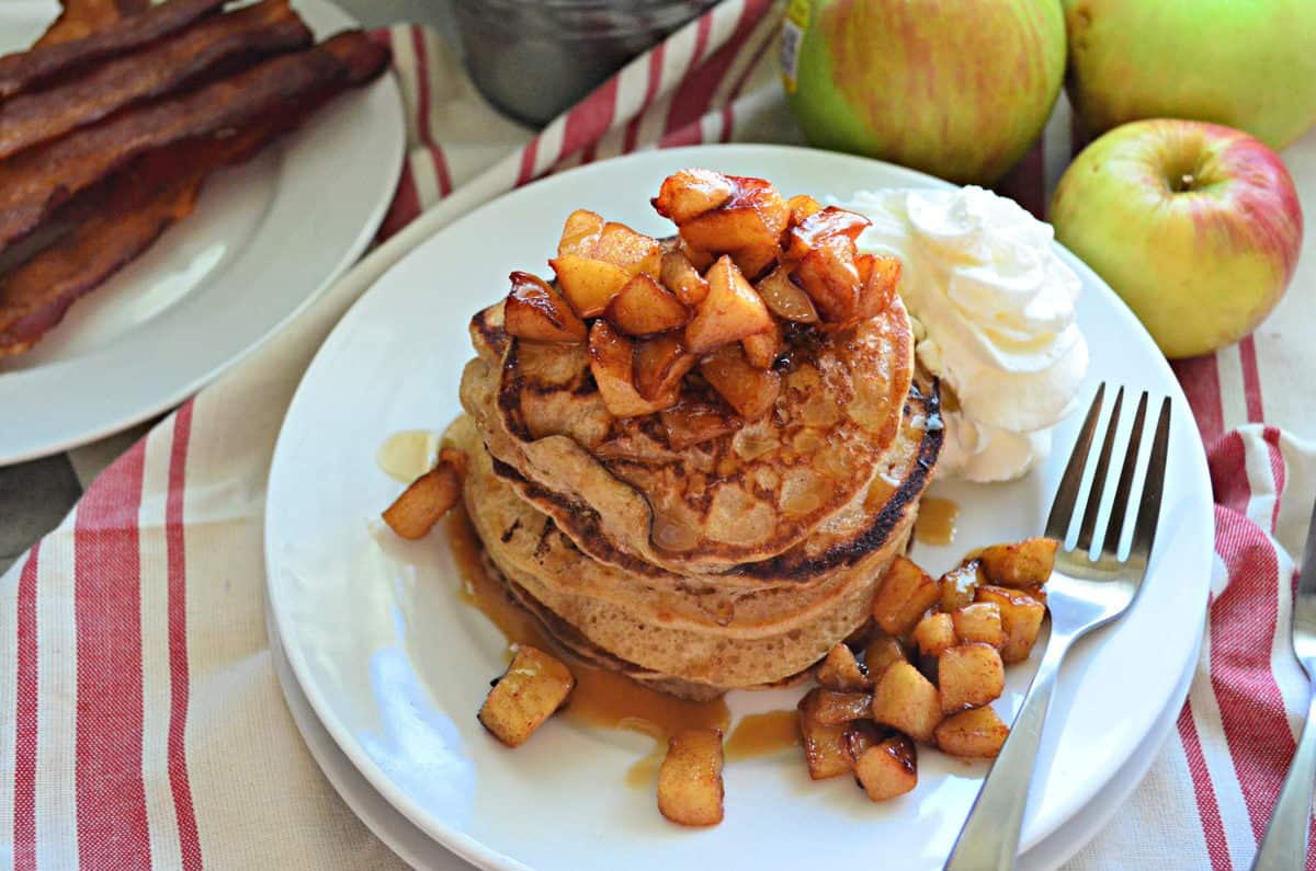 top view stack of cinnamon pancakes topped with cubed apples and syrup with whipped cream.
