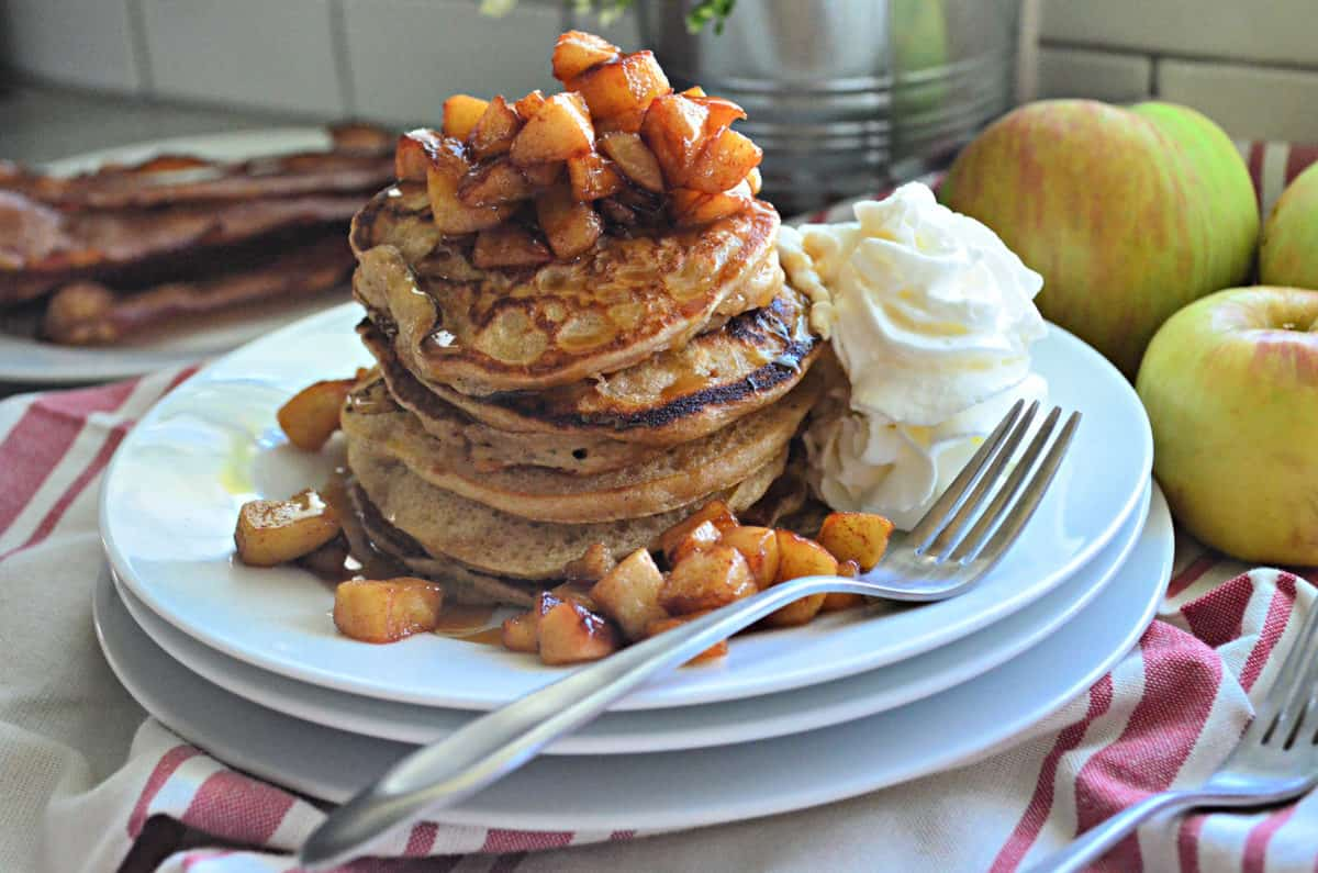 side view stack of plated cinnamon pancakes topped with cubed apples and syrup with whipped cream.