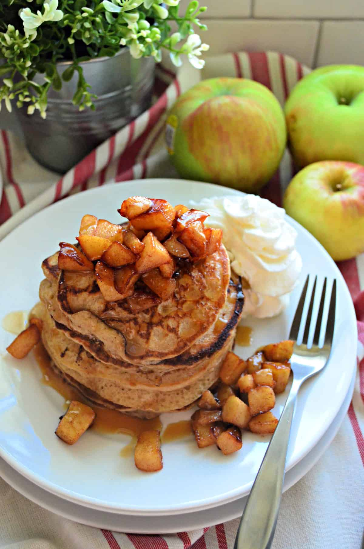 stack of cinnamon pancakes topped with cubed apples and syrup with whipped cream.