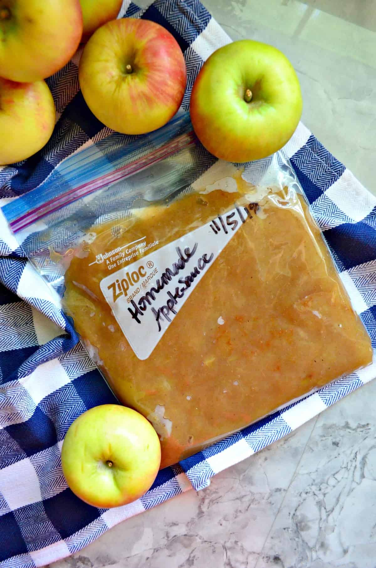 top view of labeled homemade applesauce in ziplock bag with apples on tablecloth.