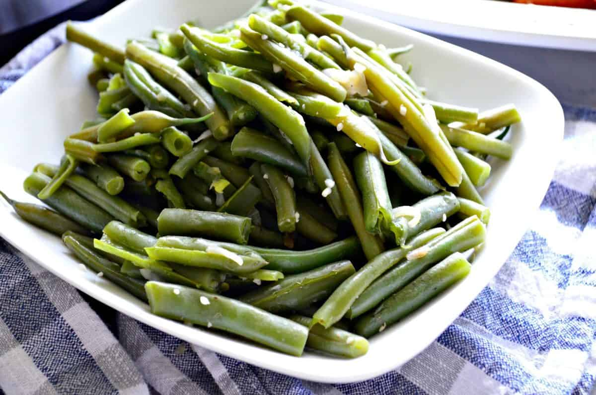 plated cooked green beans with minced garlic on top.