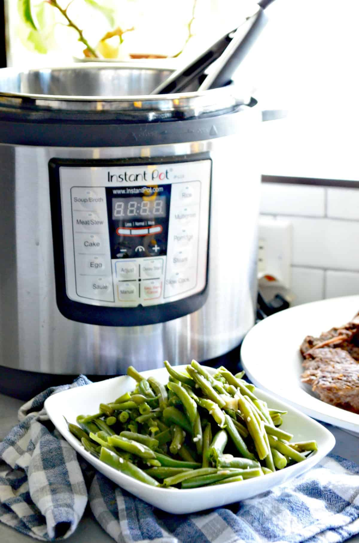 Plated cooked green beans in front of instant pot.