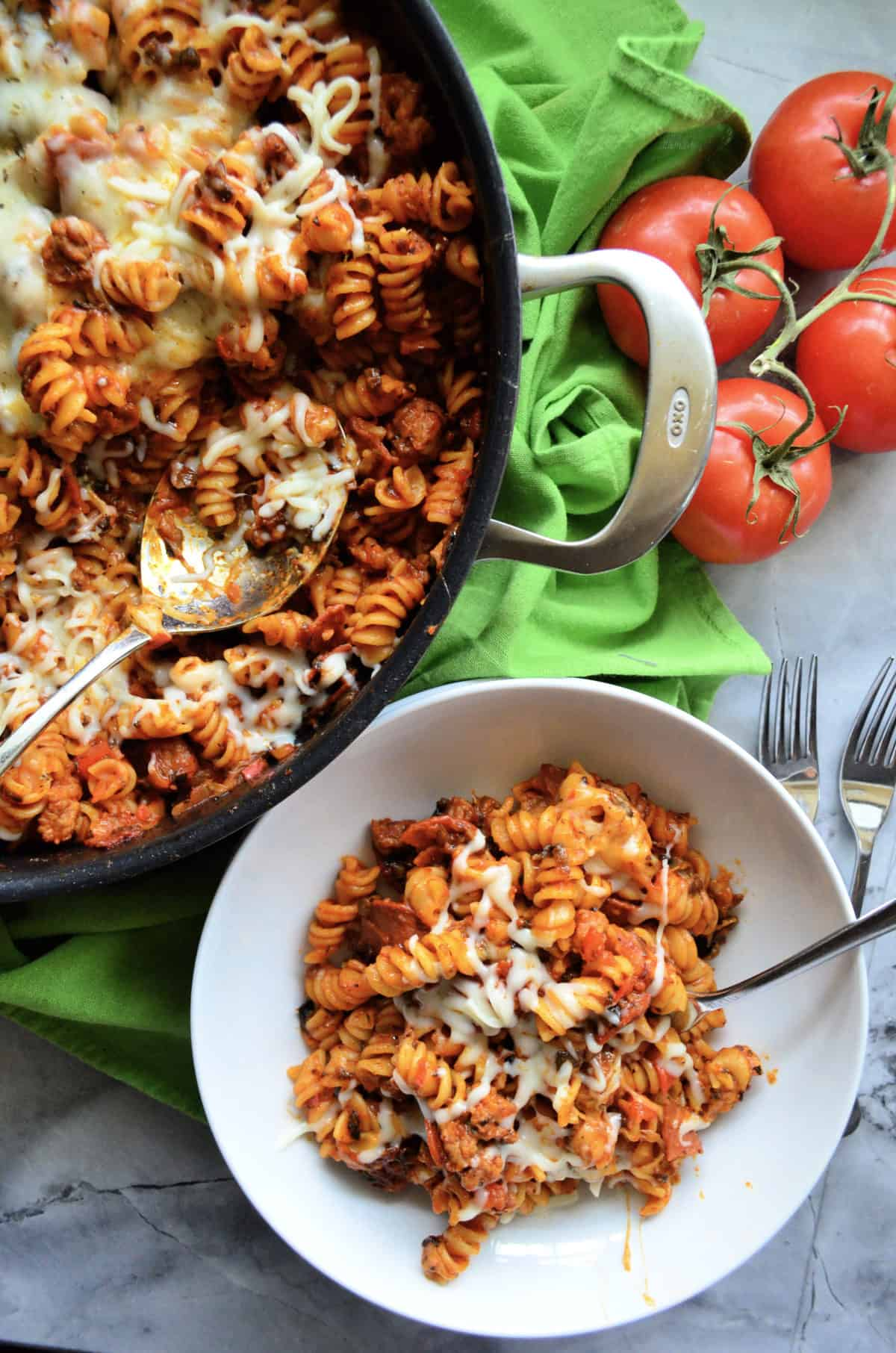 skillet and plate both with rotini in red sauce topped with herbs and melted white cheese.