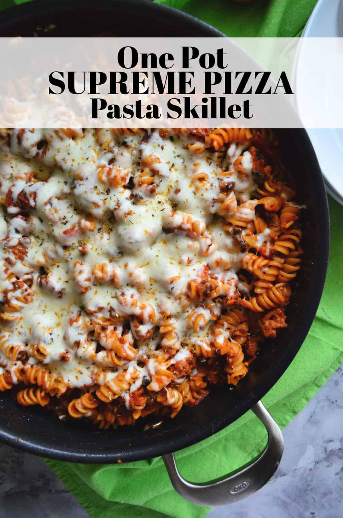top view of skillet with rotini in red sauce topped with herbs and melted white cheese with title text.