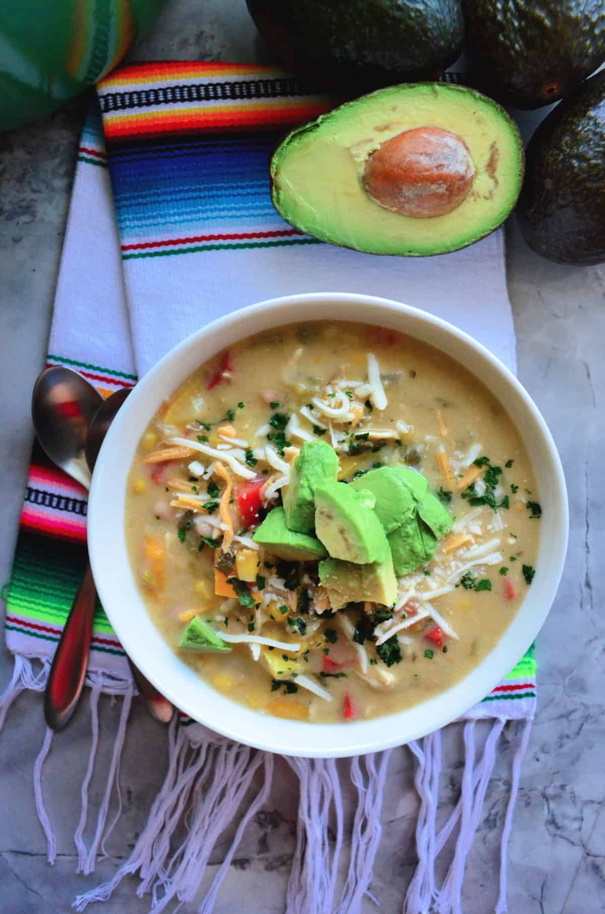 Green Enchilada Chicken Soup in bowl topped with cheese and avocado next to halve avocado.