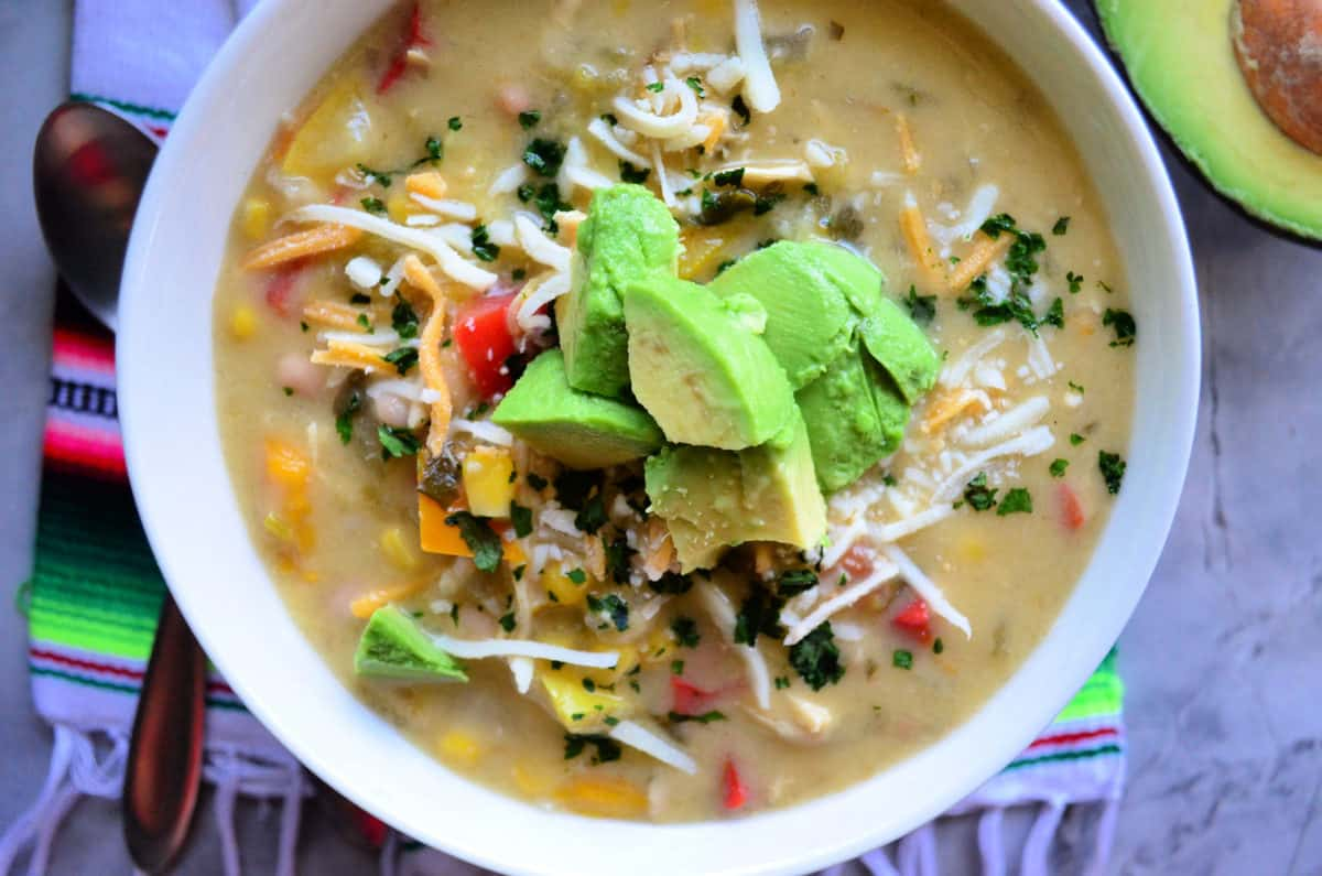 top view Green Enchilada Chicken Soup in bowl topped with cheese and avocado on colorful cloth.