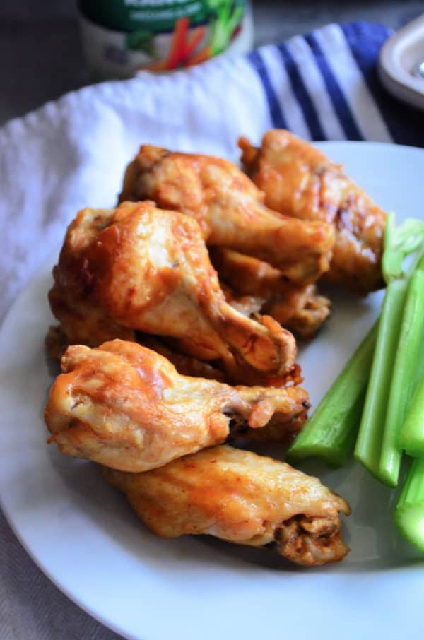 stack of chicken wings on plat next to celery.