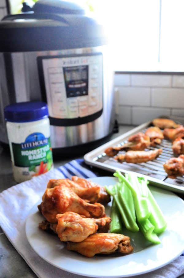 stack of chicken wings on plate with celery in front of instant pot.