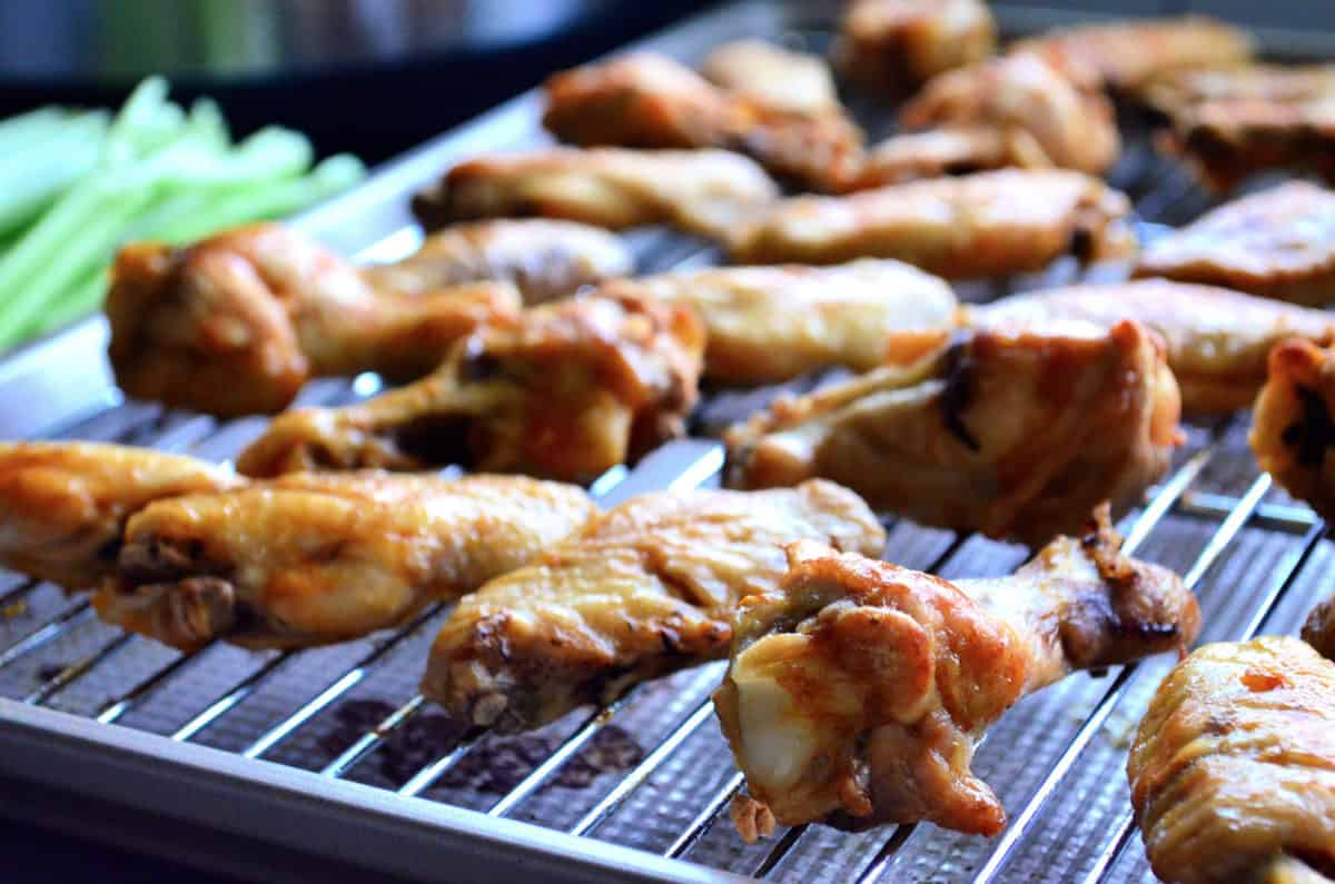 side view chicken wings on metal rack placed on sheet pan with celery blurred in background.