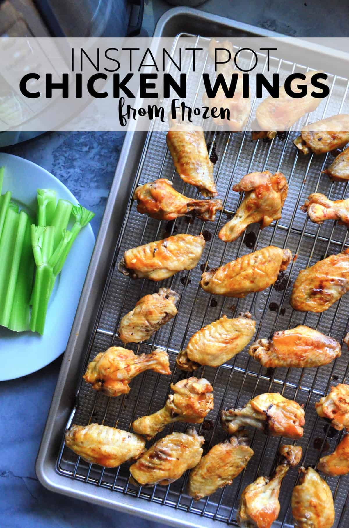 Top view chicken wings on metal rack placed on sheet pan next to celery plate with title text.