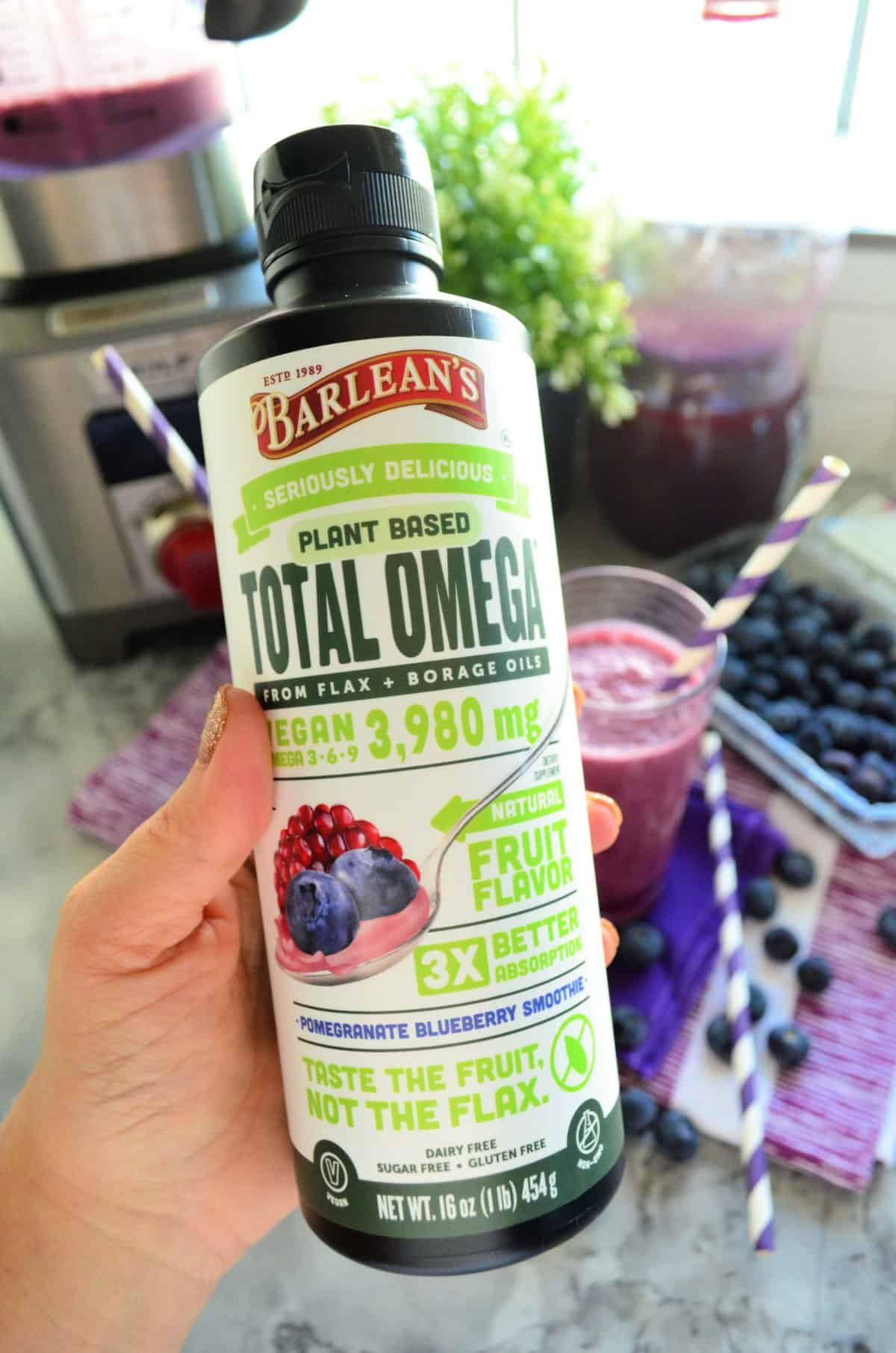 Barlean's Plant Based Total Omega from flax bottle being held close up with smoothies in background.