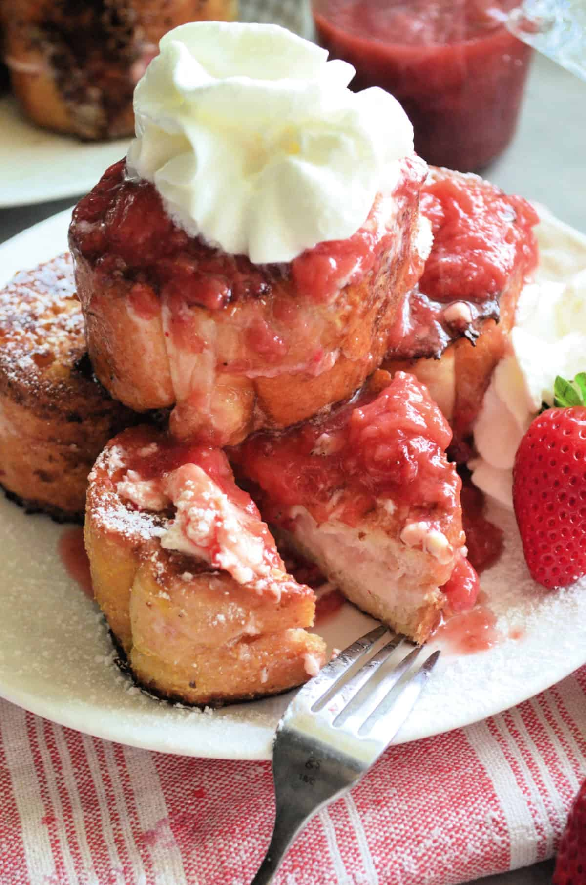 closeup stacked Strawberry Cream Cheese Stuffed French Toast with whipped cream and strawberries.