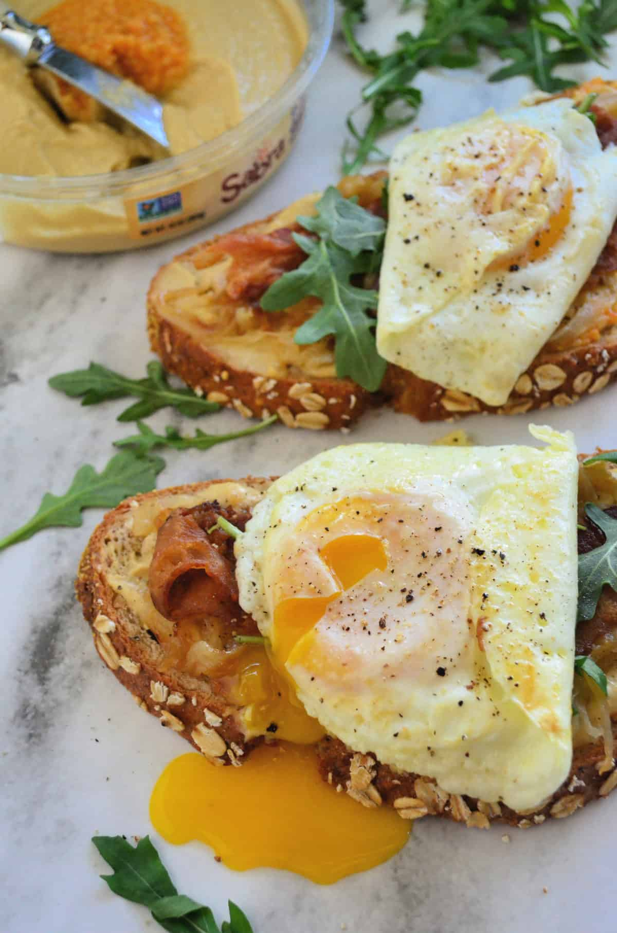 bread topped with hummus, bacon, over easy eggs oozing yolk, and arugula on platter.