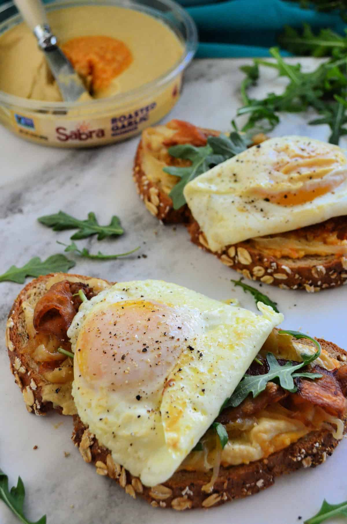 bread with hummus, bacon, over easy eggs oozing yolk, and arugula on platter with hummus behind.