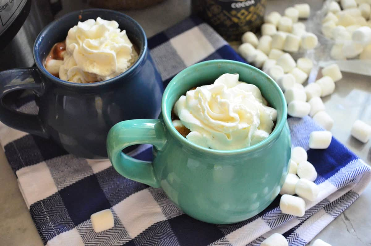 two mugs with whipped cream showing from the top on checkered tablecloth with mini marshmallows.
