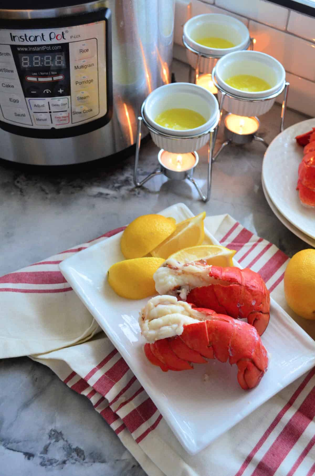 Two plated lobster tails with lemon and hot butter on tablecloth in front of instant pot.