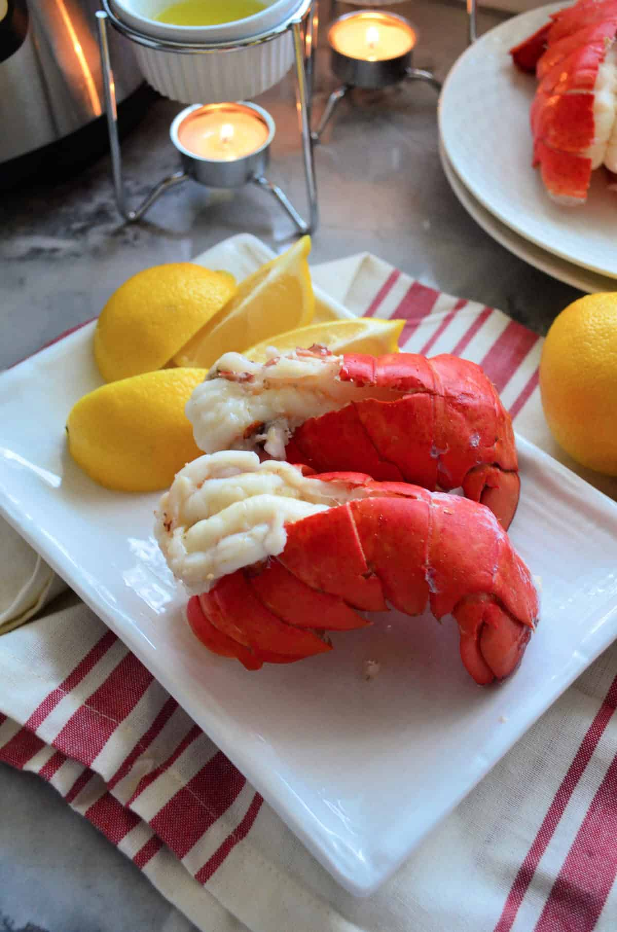 top view 2 plated lobster tails served with lemon wedges.