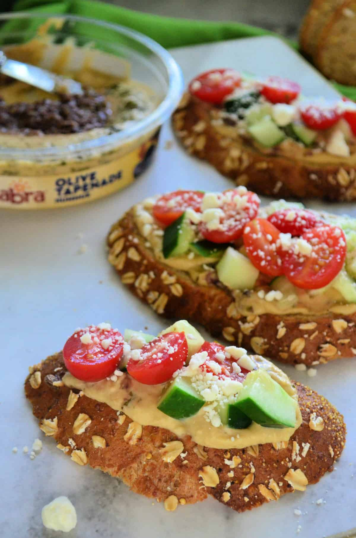 3 toast slices topped with hummus, cucumber, tomato, and feta with sabra hummus blurred behind.