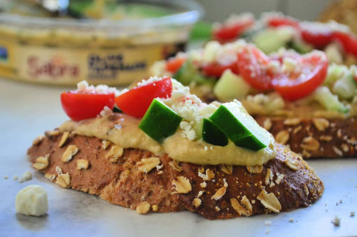 closeup side view of toast slice topped with hummus, cucumber, tomato, and feta.