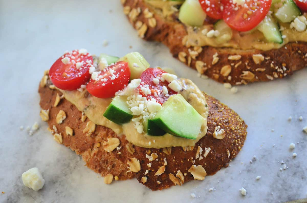 top view of toast slice topped with hummus, cucumber, tomato, and feta.