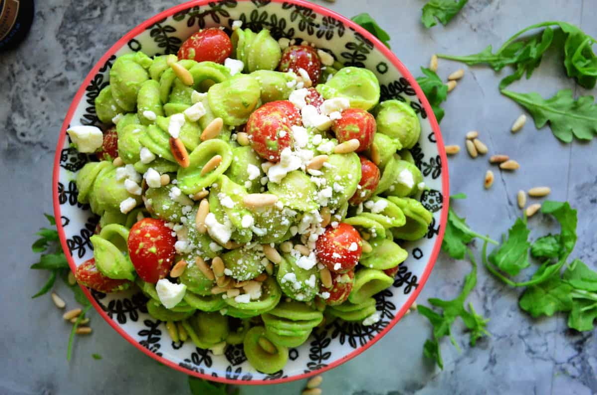 top view bowl of orrichette pasta in green sauce with pine nuts, feta, grape tomatoes on counter.
