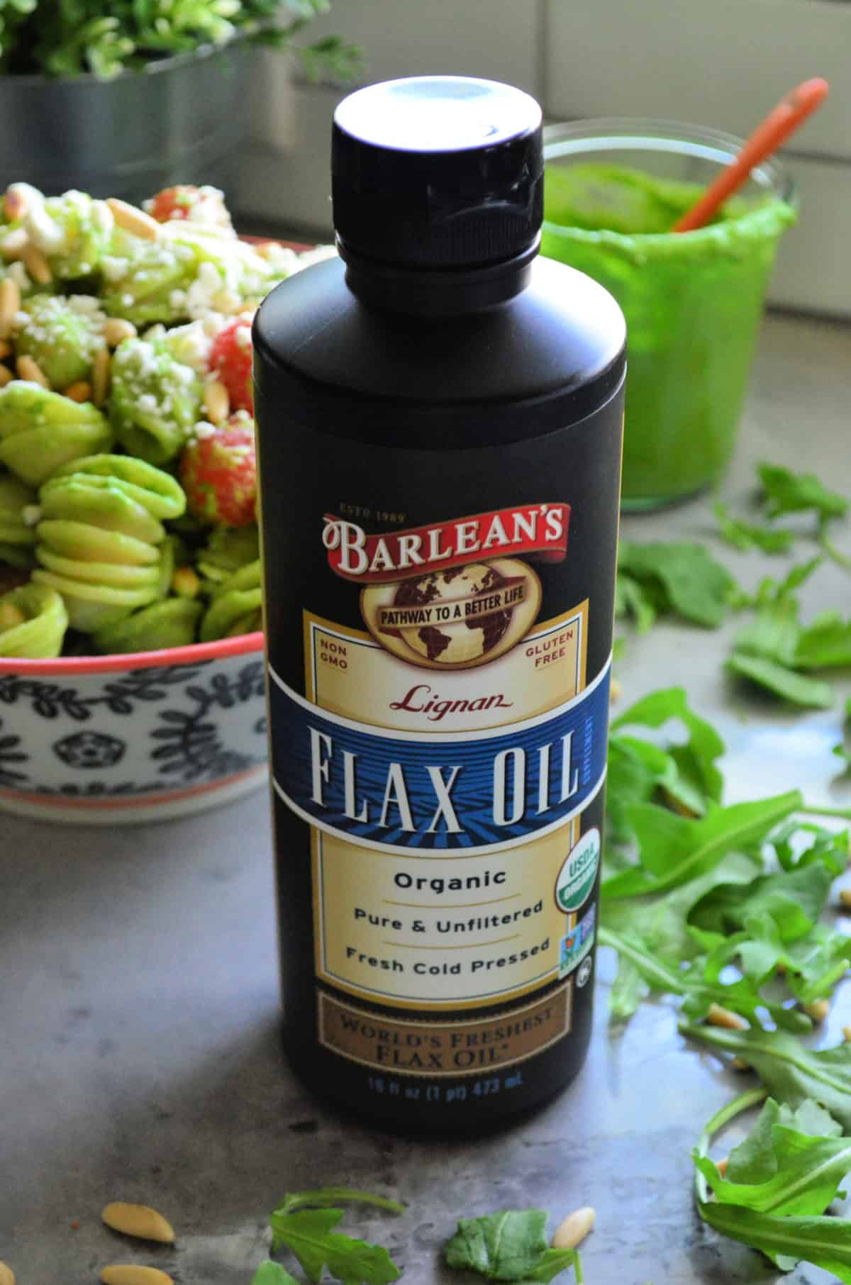 Close up bottle of Barlean's Flax Oil on countertop with pasta salad blurred in background.