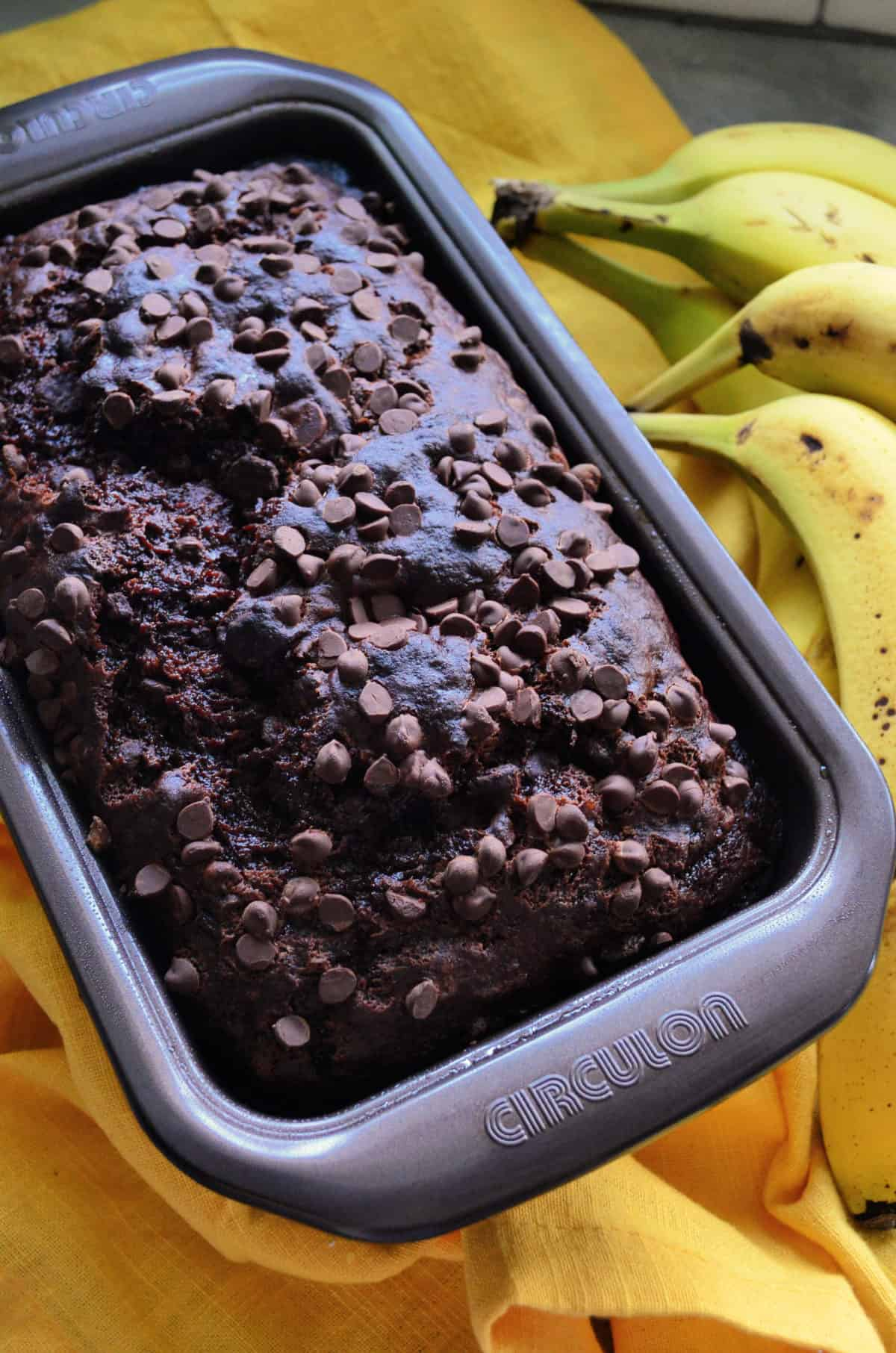 Top view of loaf of brown bread in pan with chocolate chips in it and bananas in background.