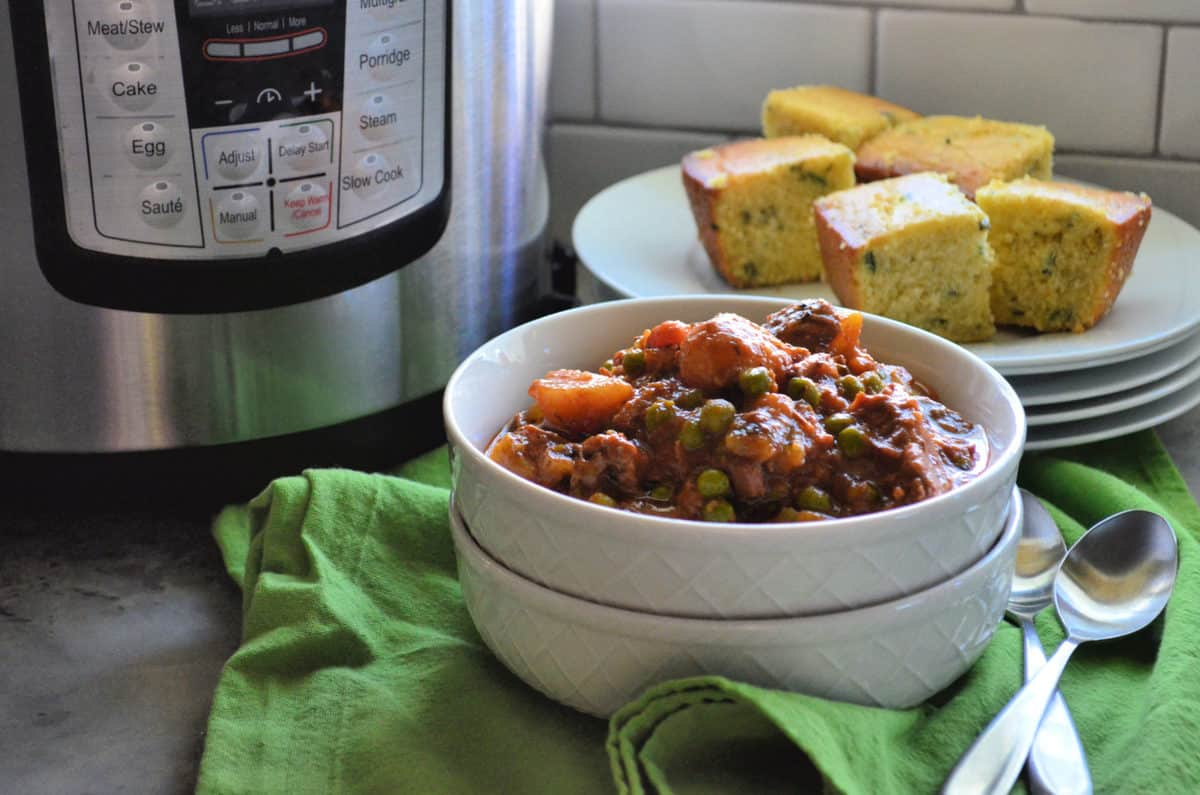 Bowl of beef stew with potatoes, peas, and carrots in front of instant pot and corn bread.