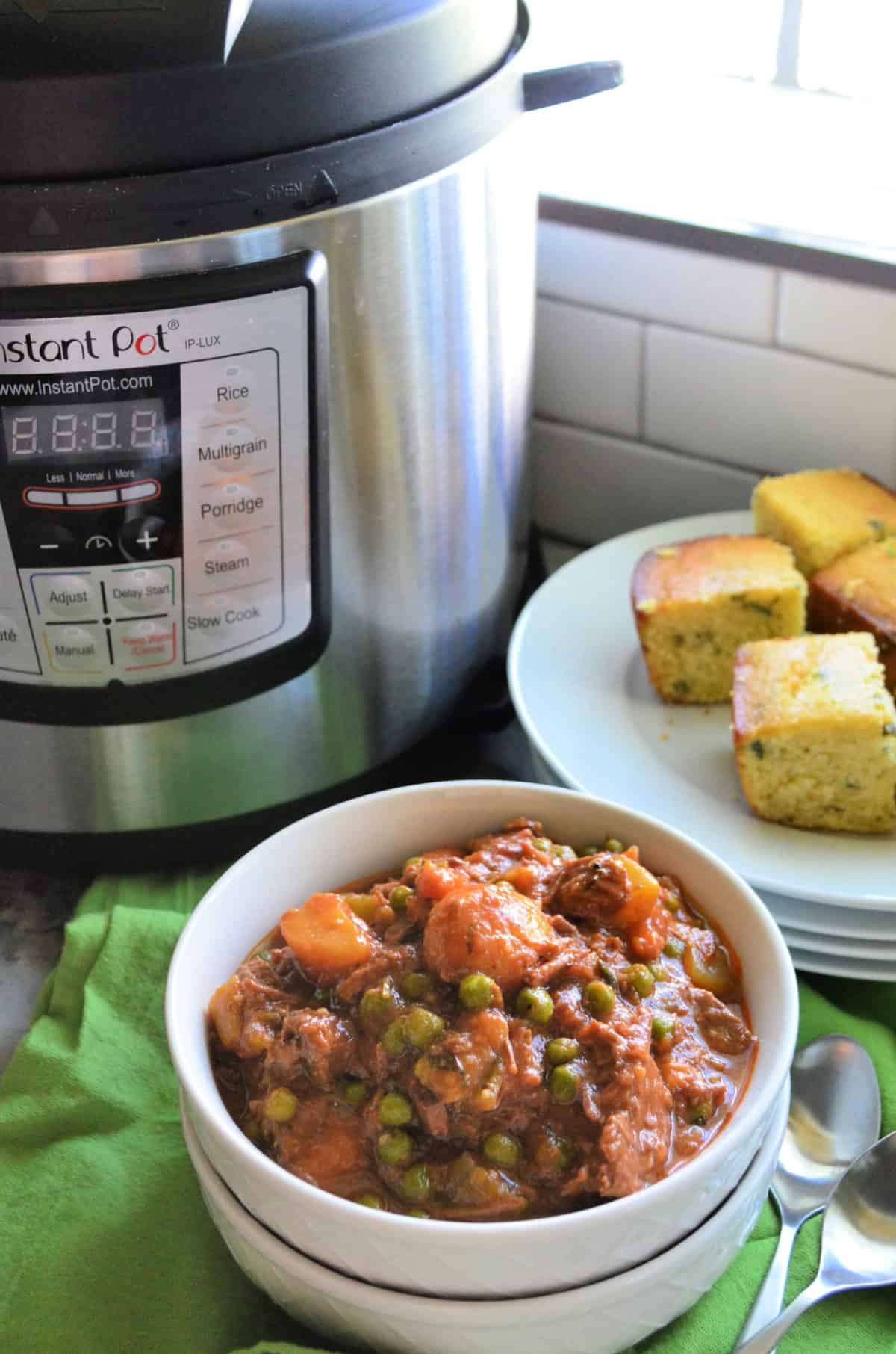 Closeup bowl beef stew on green cloth with corn bread and Instant Pot behind it.