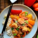 top view of bell peppers, shrimp, green onions topped with sesame seeds plated on bed of rice with chopsticks.
