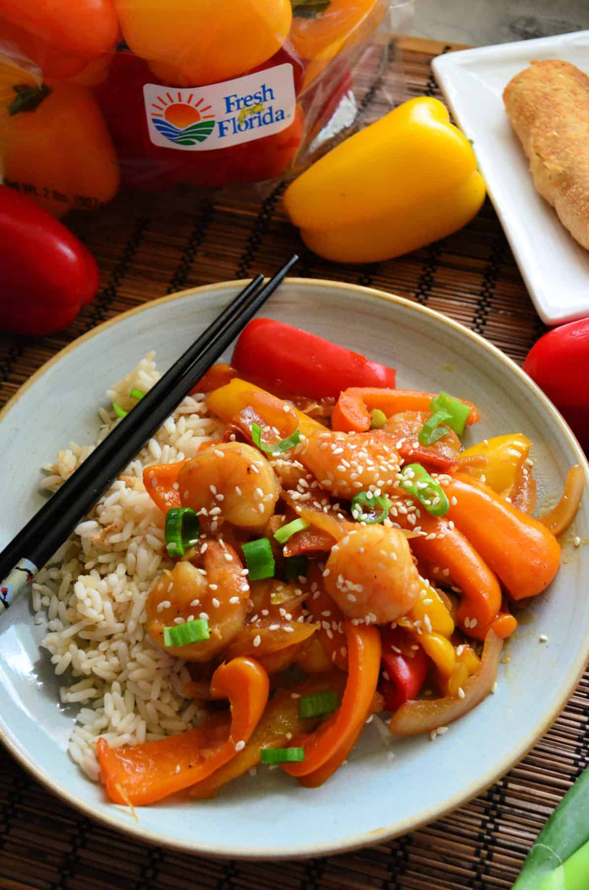 sauce, shrimp, peppers, green onions, and sesame seeds over plated rice bed with chopsticks.