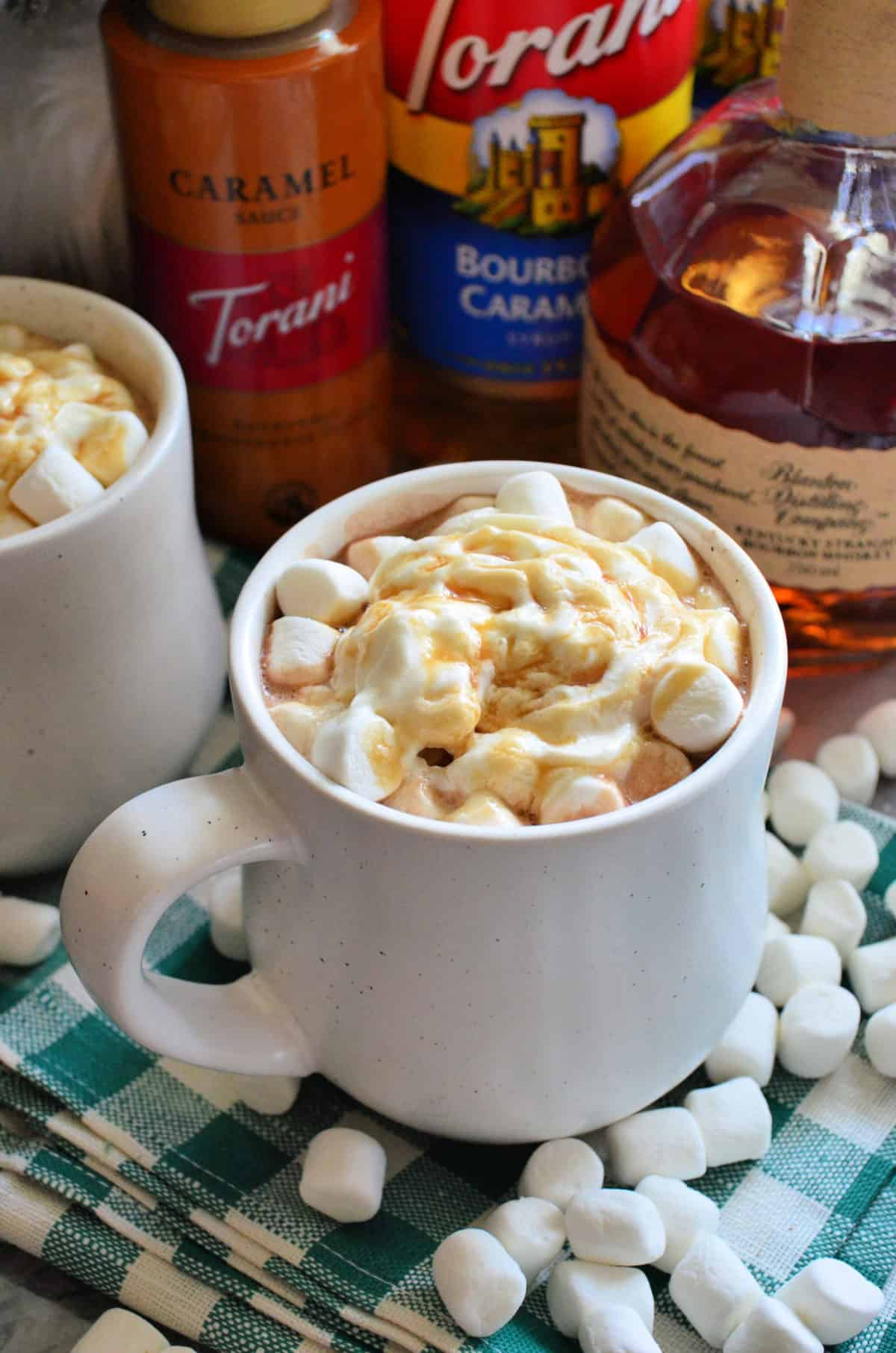 two mugs of brown liquid topped with mini marshmallows, whipped cream, and caramel with ingredients behind.