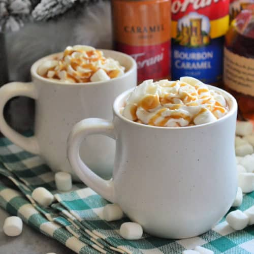 Two mugs on tablecloth with whipped cream and caramel drizzle showing from mug tops.