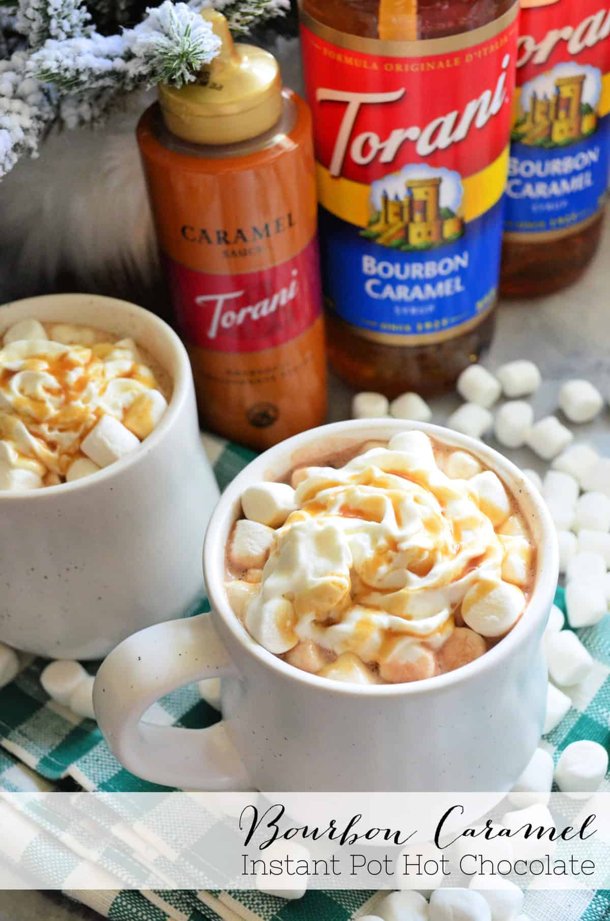 two mugs of brown liquid topped with mini marshmallows, whipped cream, and caramel with title text.