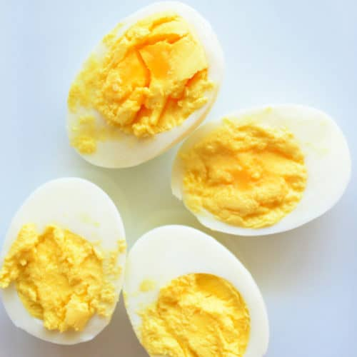 two halved hard boiled eggs with yolks facing up and pinterest title text.