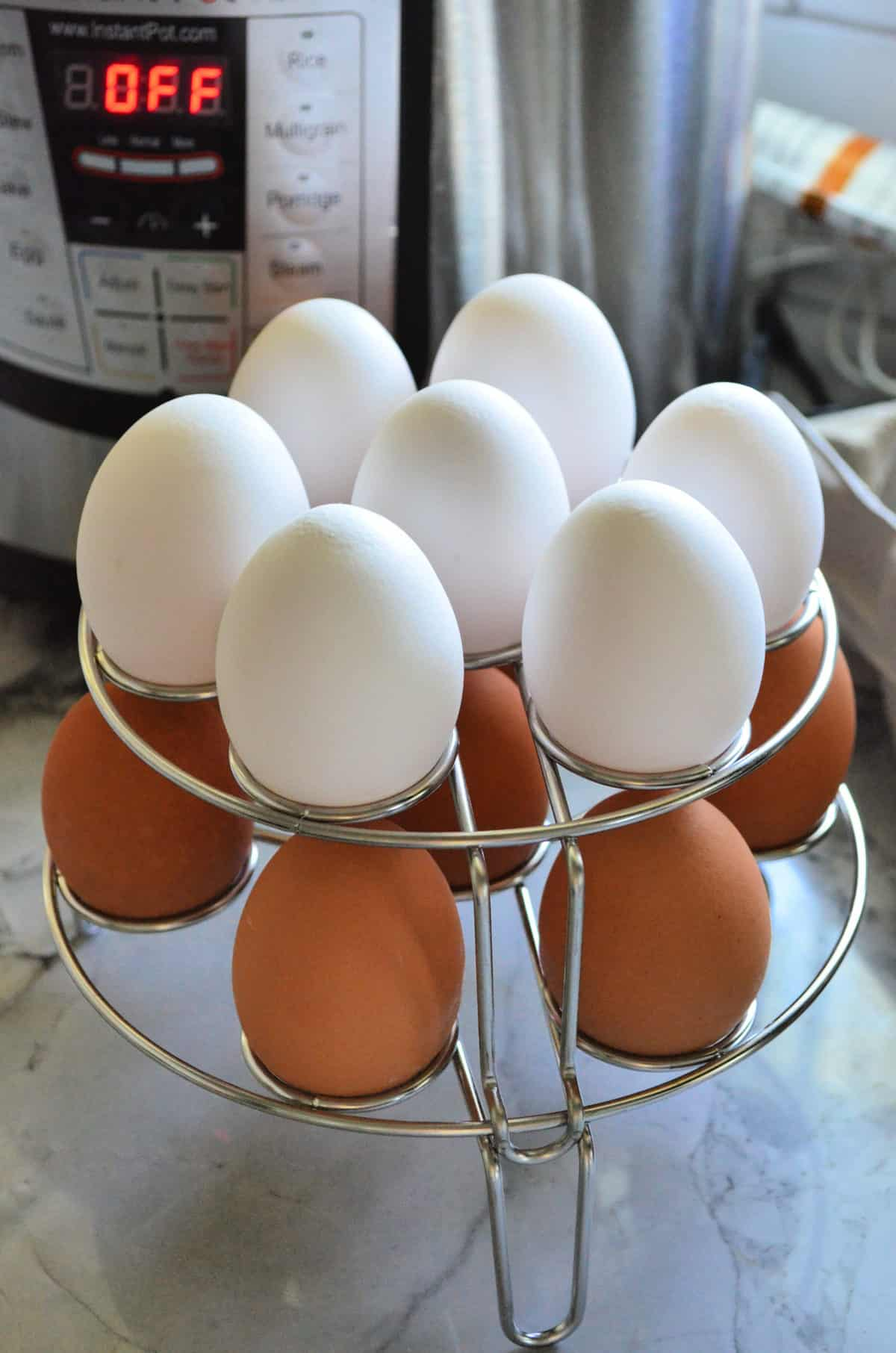 14 eggs resting on 2-level wire egg rack in front of instant pot.