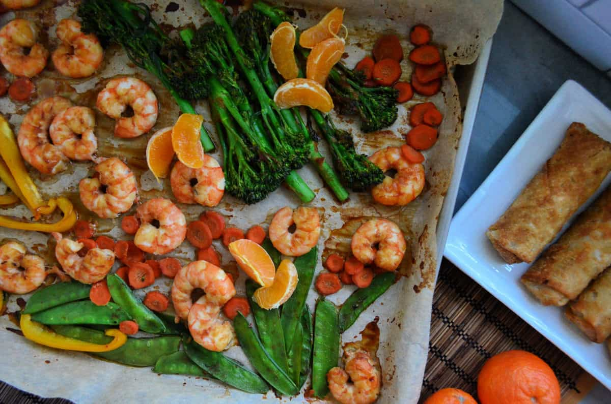peas, broccolini, mandarine oranges, shrimp, bell pepper, and carrots on paper on baking sheet.