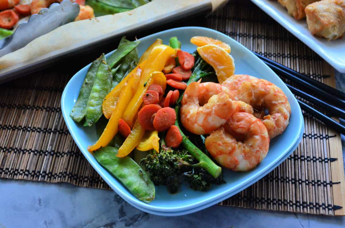 Square plate with shrimp, broccoli, bell peppers, carrots, and peas.