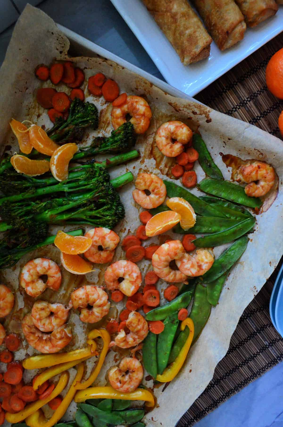 closeup peas, broccolini, mandrine oranges, shrimp, bell pepper, and carrots on paper on baking sheet.