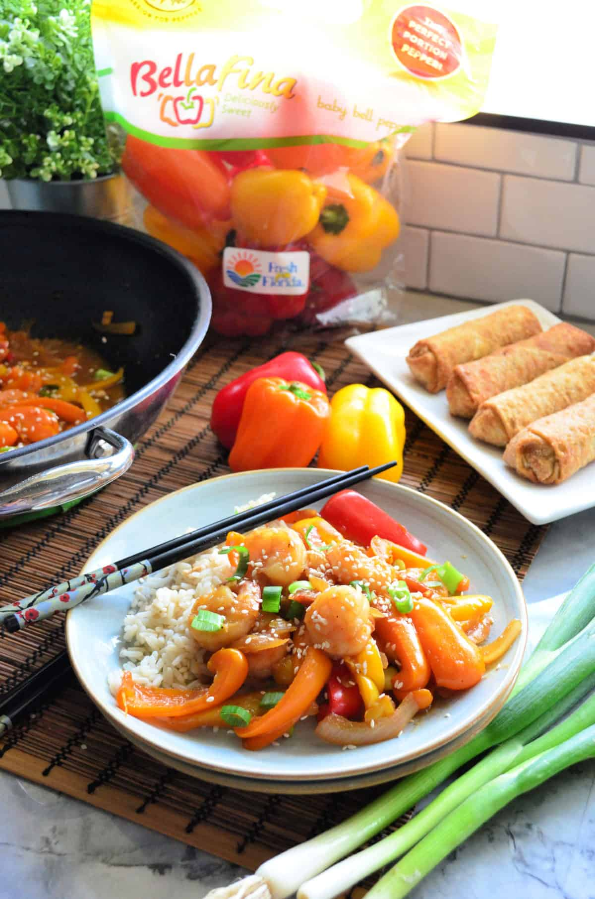 Plated Shrimp and Sweet Pepper Stir-Fry with rice in front of wok, peppers, and egg roll platter.