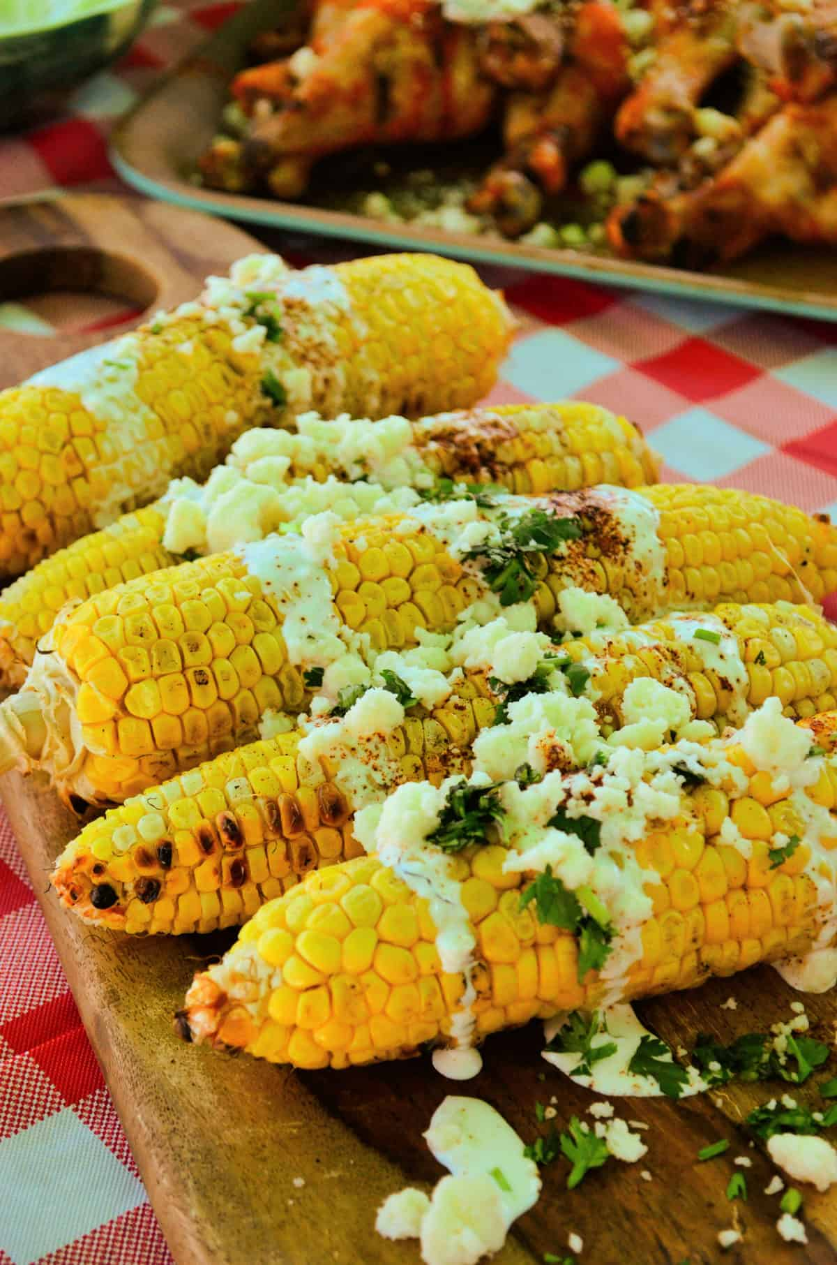 corn cobs on a board drizzled with crema, cheese crumbles, red powder, and herbs.