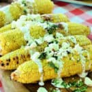 side view Grilled Mexican Street Corn resting on wooden board on picnic tablecloth.